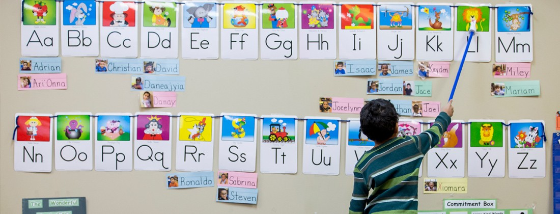 Child pointing at letters of the alphabet on wall display
